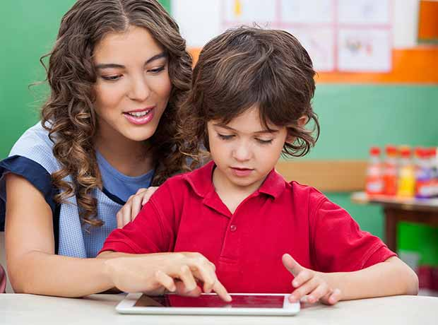 Photo of a teacher showing a young boy something on an iPad.