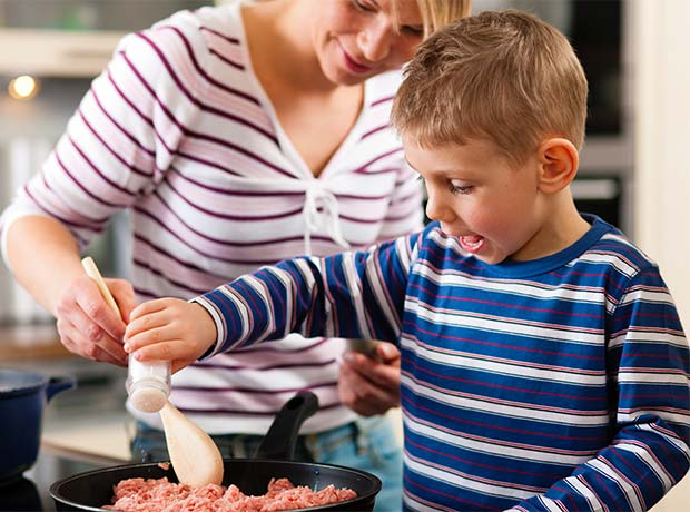 photo of a young boy cooking, helped by a teacher.